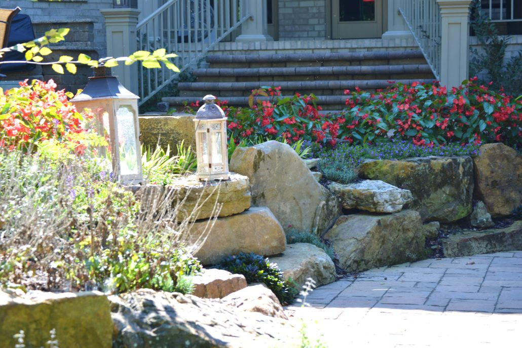 Hardscape stones and paver, surrounded by annual flowers and professional landscaping