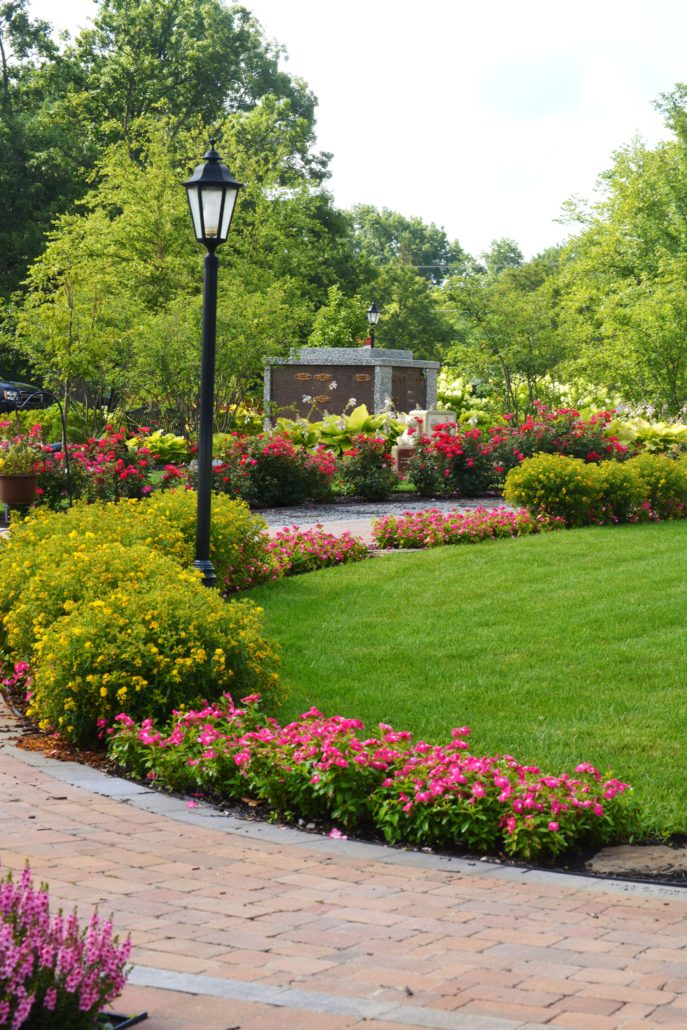 Brick walkway surrounded by planted flowers